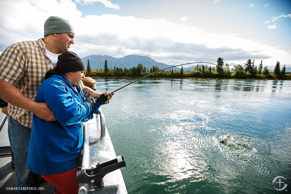 Nadia reels in a fish with the help of her husband, Scooter. The couples can enjoy fishing from the camp's specially-equipped boat, or to fly fish while standing in the pristine waters of Alaskan lakes.