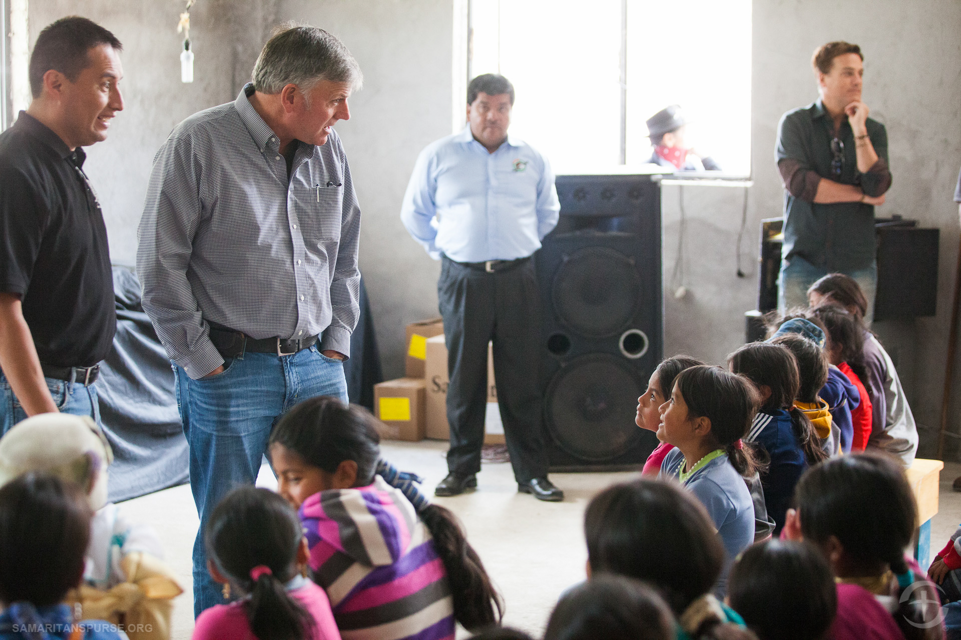 Franklin Graham speaks with local children before handing out shoe box gifts.