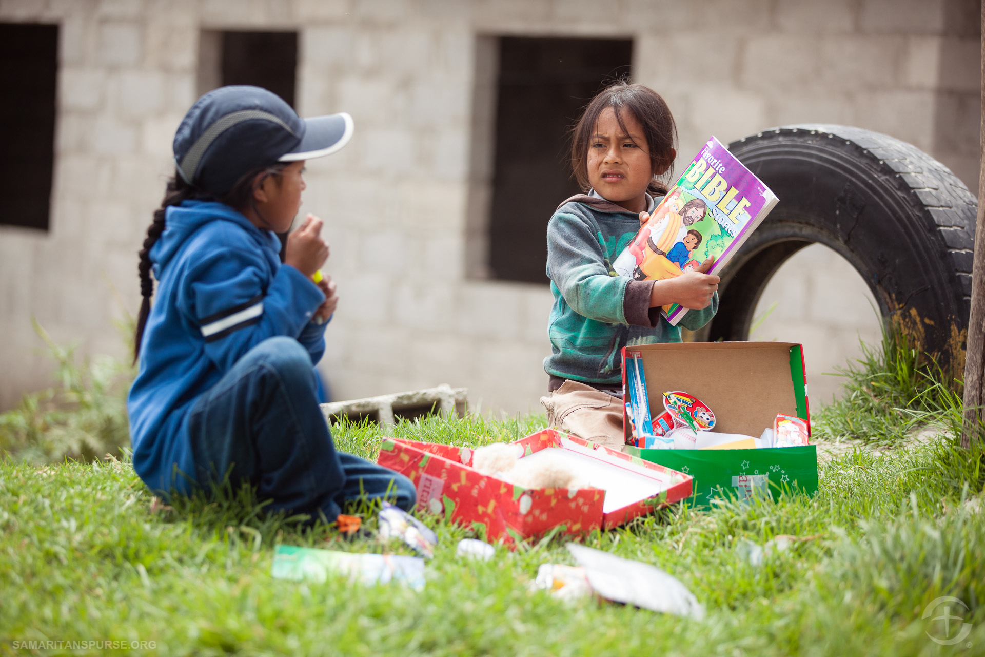 Children discover what's inside their boxes. Gifts like coloring books, hygiene items, and small toys make a huge impact on children who may have never received a gift before.