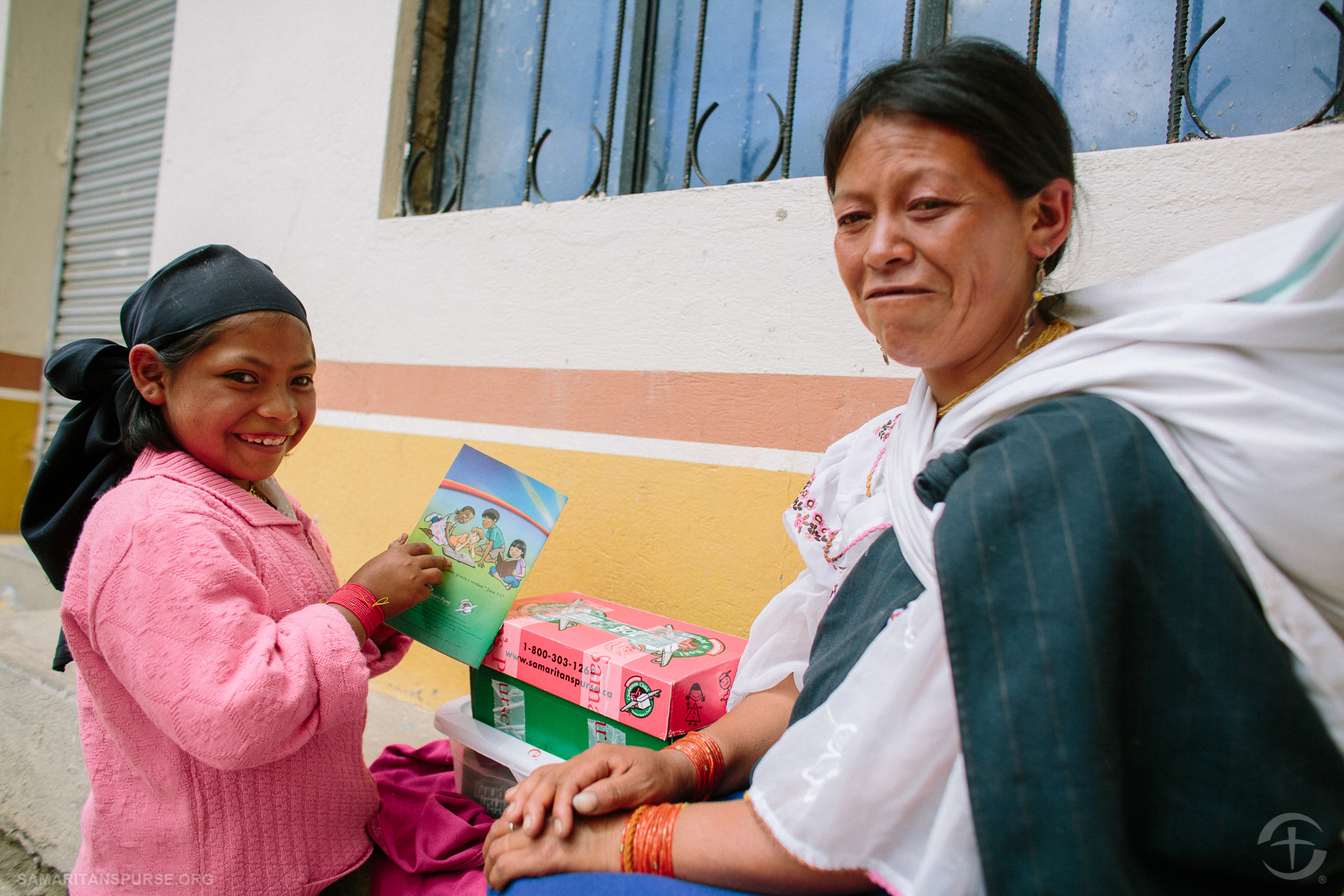 A little girl looks at the reading material offered with her shoe box gift. Each child received a booklet explaining that Jesus is the greatest gift of all. Afterward, many children have the opportunity to join a 12-week discipleship program called The Greatest Journey, where they learn more about faith in Jesus Christ and developing a deeper relationship with Him.