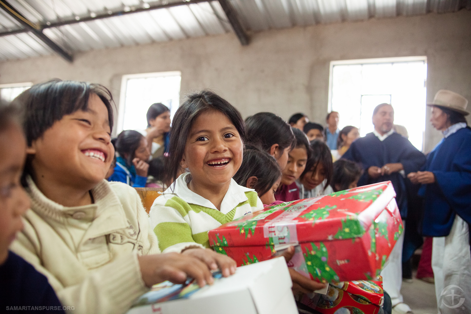 Children eagerly await the moment they are told to open their shoe box gifts.