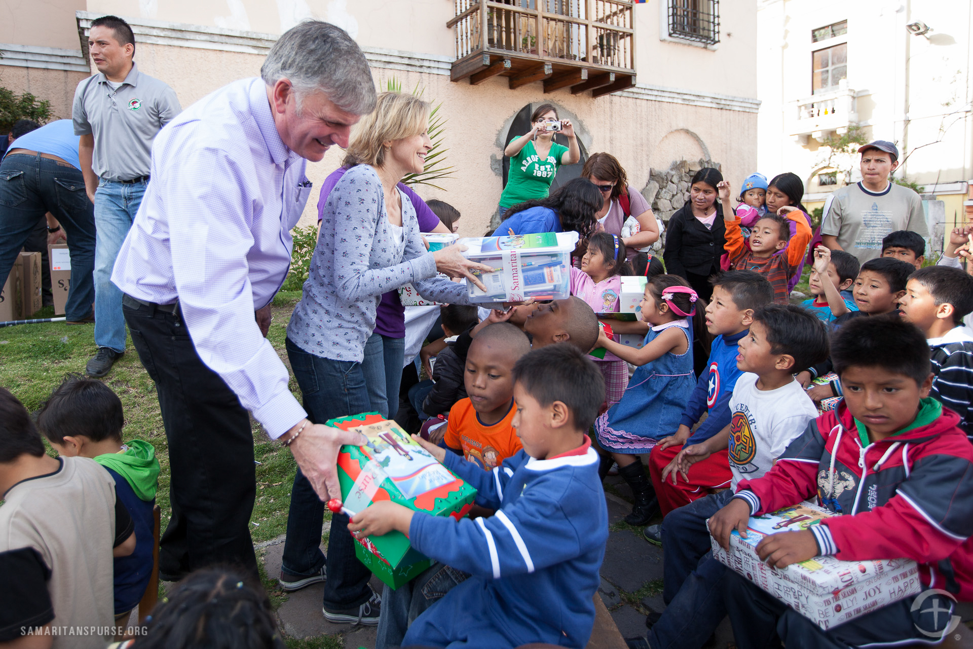 Michael W. Smith's wife Debbie helps Franklin Graham hand out shoe boxes.