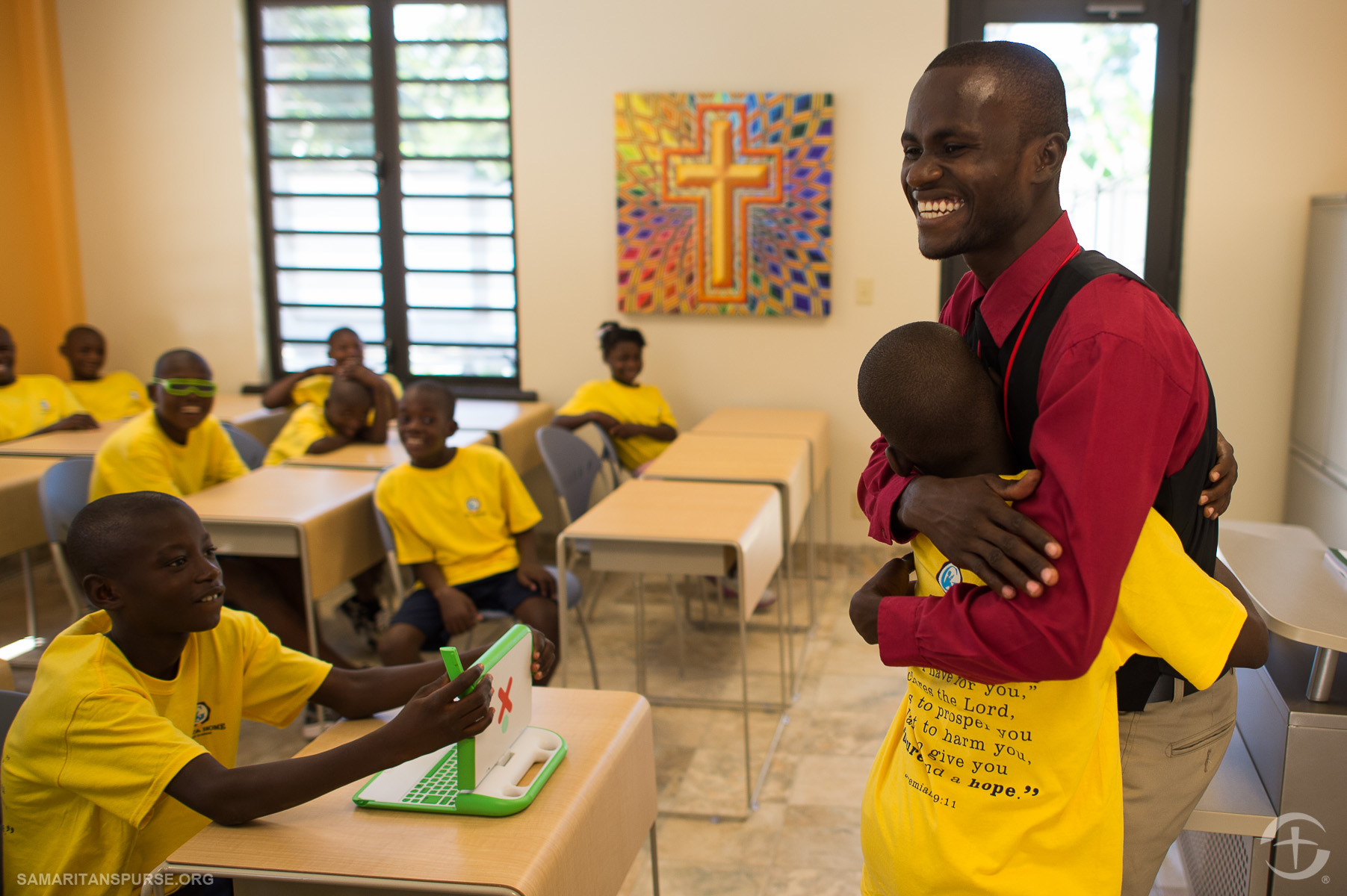 Translator Marc Edwine Cherisme hugs one of the 73 children now living at Greta Home and Academy. Linguistics is an emphasis of the school; classes will be taught in Creole, French, and English (English class).