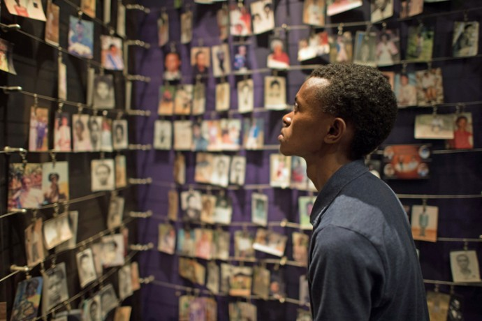 Alex looks at photos of genocide victims on display at Kigali Genocide Memorial Center.