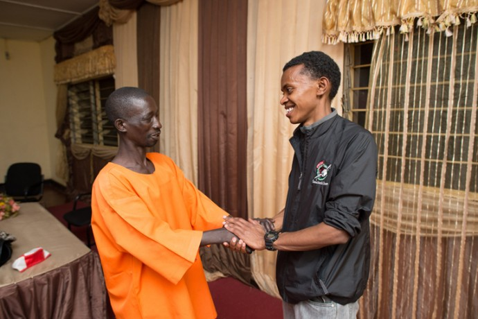 Alex shakes hands with the man who killed his uncle, Niyoneza Anastase, in Nyarugenge Prison in Kigali, Rwanda.