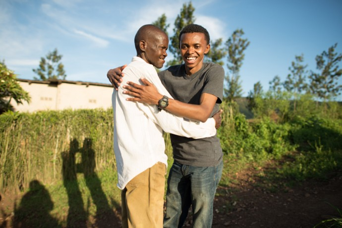 – Alex and his remaining uncle, Rusanganwa, embrace next to a garden planted on the land where their house used to stand in Butamwa, Rwanda.