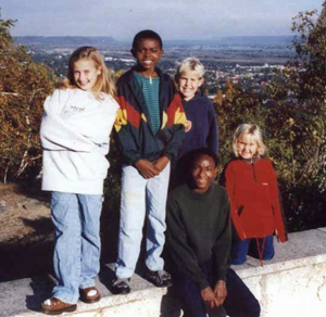 On their Choir tour in 1999, Alex (second from left) and his friend Alphonse spent three days with a family in Minnesota. In 2003, the boys were sponsored by that family to come to the United States for an education.