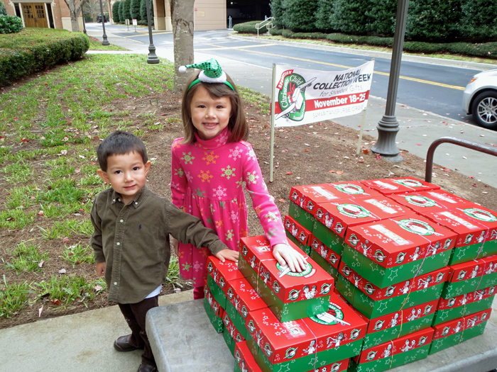 Isaac, 4, and Kate, 6, deliver the shoebox gifts to a collection site.