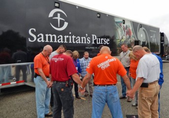 Staff and volunteers pray before heading out to help homeowners impacted by the floods.