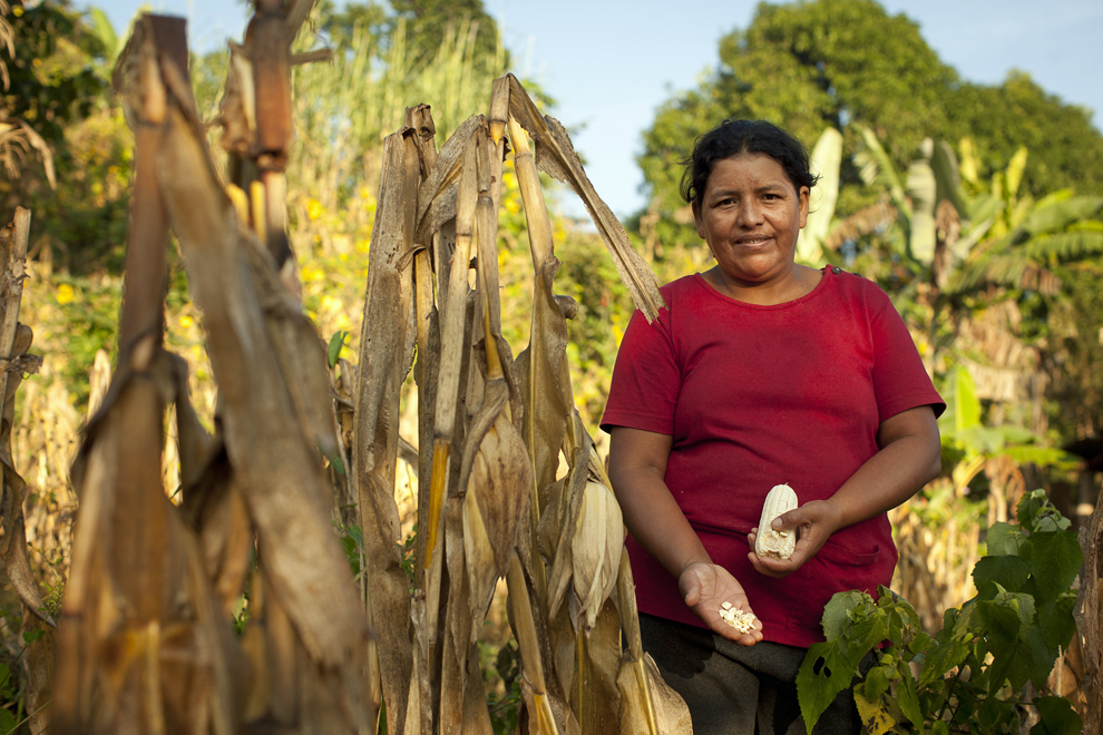 A Honduran woman displays some of her harvest, a gift she is very thankful for.