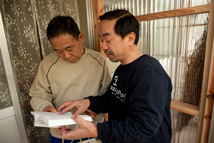 Pastor Dave Kazama presents a Bible to a resident of Kesennuma living in a temporary housing unit.