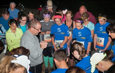 Darren Mullenix, director of Team Samaritan's Purse, leads the runners in a prayer before the race.
