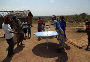 Villagers look on as the benefits of a solar cooker are demonstrated.