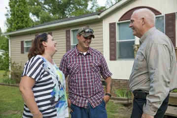 Jeremiah and Janice Marcum share a light moment with Pastor Pat Fleming in front of their home.