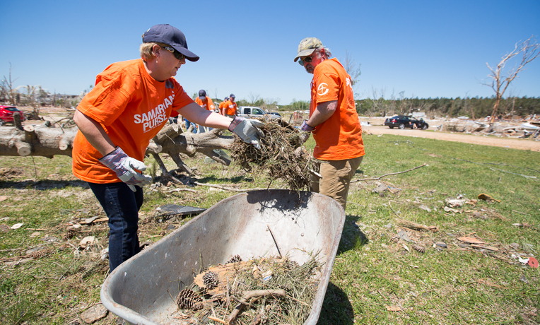Mississippi First Lady Deborah Bryant helps clear debris from the yard of James and Glendette Roberson.