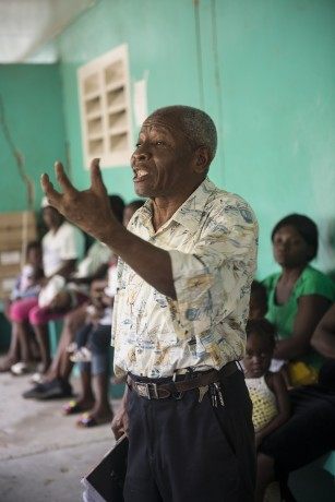 A pastor speaks words of hope to patients waiting to be seen at the Samaritan's Purse medical clinic in Cite Soliel.