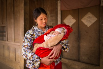May holds her second child outside her home. She benefited from having the baby while also taking classes to become a traditional birth attendant.