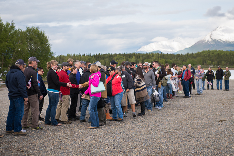 A long line of greeters, including the Ticknors, welcome military couples to Port Alsworth, Alaska.