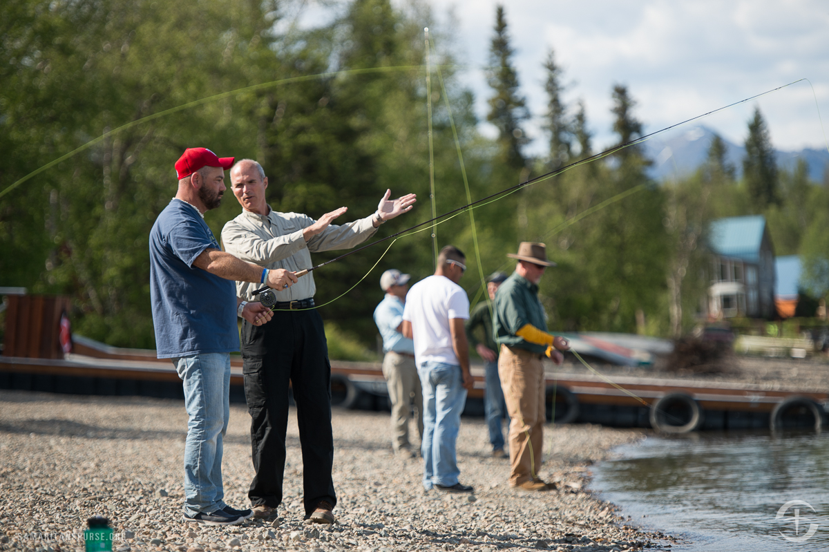 Retired Marine Brigadier General Jim Walker, executive director of Operation Heal Our Patriots, gives James Taylor some pointers on fly fishing while other men also practice their casting.