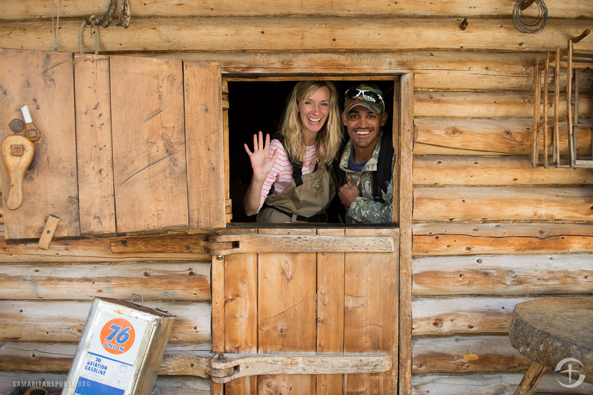 """Retired Army Sergeant First Class Junior Murguia and his wife Heather of Osceola, Missouri, pose at the much-photographed entrance to Proenneke's cabin. Junior served in Iraq and Afghanistan and suffers with PTSD and a back injury that wakes him up in pain each morning. """"It's an everyday battle,"""" he said. """"Because my back is a combat injury, it really triggers my PTSD."""""""