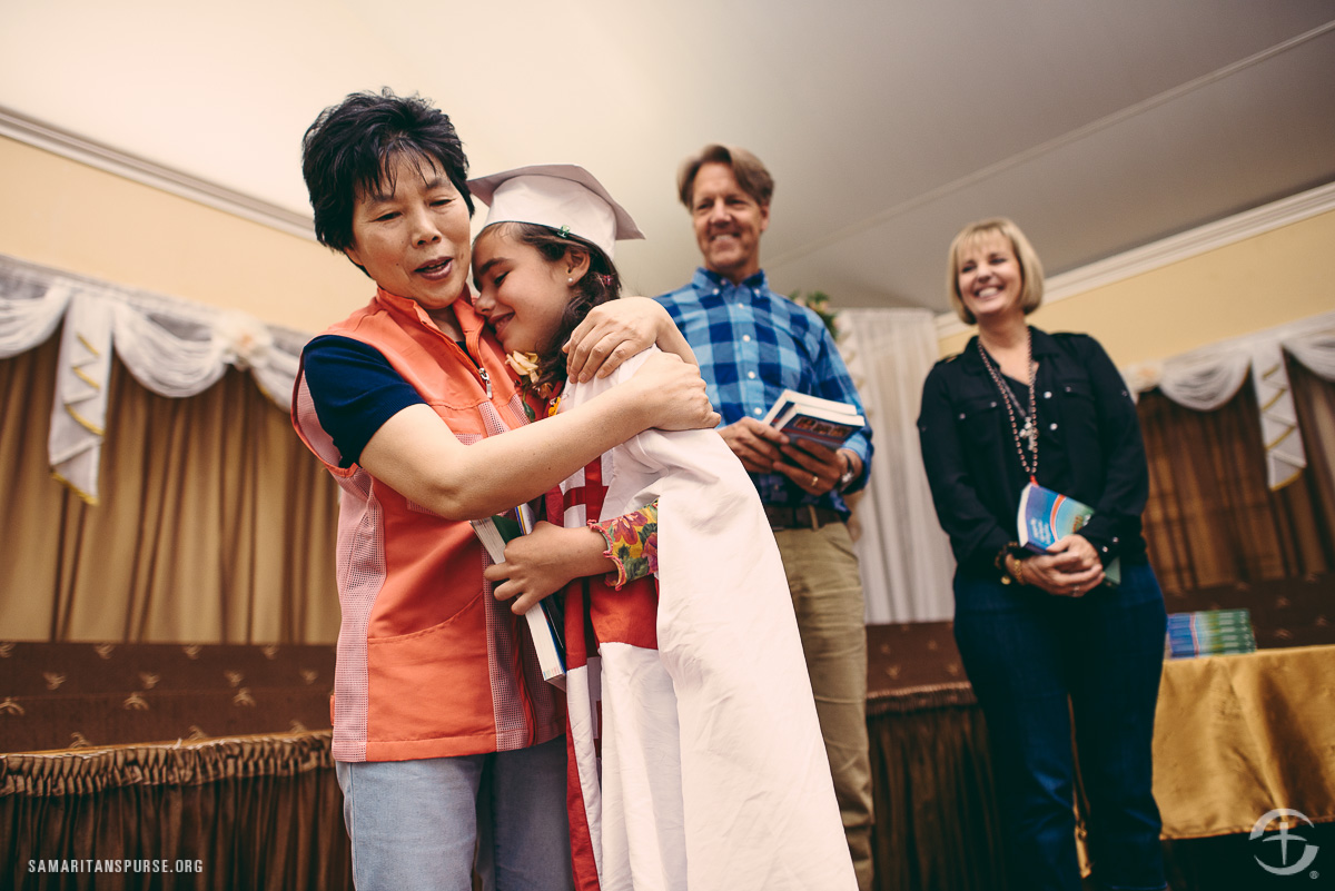 Nina hugged the children as they walked across the stage. Although they have completed The Greatest Journey, they won't stop attending Nina's classes. She will continue to teach them and help them grow in their faith.