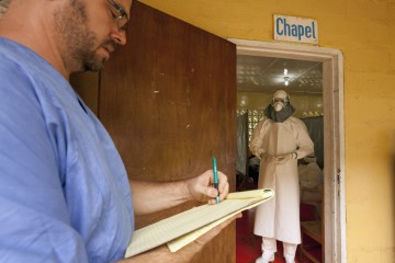 Dr. Kent Brantly gives orders for medication to administer to the Ebola patients through the doorway of the isolation unit. Dr. Brantly spent almost four hours in the Tyvek suit in order to care for the three patients in the unit.