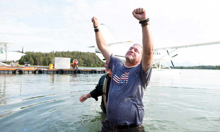 Retired Army Sergeant Conrad DeGrace, Jr., of Galveston, Texas, raised his arms in victory after being baptized. The week in Alaska's wilderness reinvigorated his faith walk with Christ. He and his wife, Trish, also rededicated their marriage.