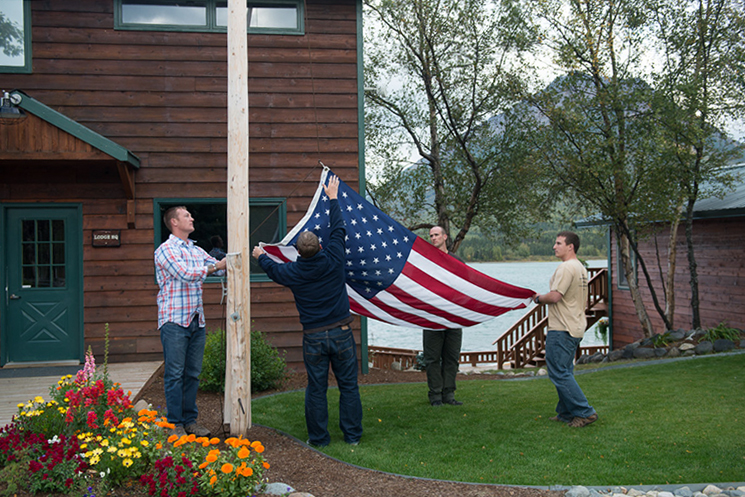 Active-duty Army Rangers Blake Clotfelter, Patrick Hartung, Kris Newville, and Tom Wright lower the flag.