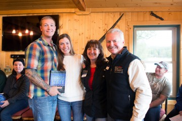Patrick and Jennifer Hartung receive a new Bible, signed by staff, from the Langs. Mark Lang is program manager for Samaritan Lodge Alaska and his wife Sandy is facilities manager.