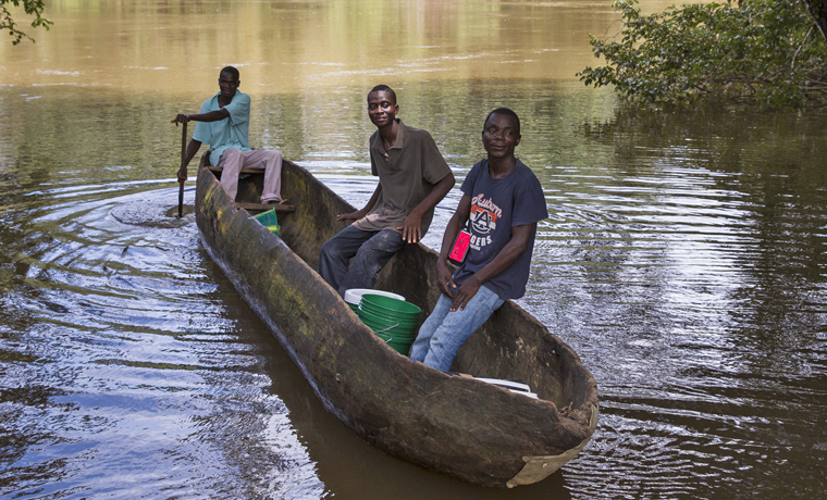 Community members transport supplies for infection protection and control kits to their village in Grand Bassa County on the River Gee.