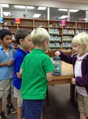 A group of first-graders contribute to the quarter jar.