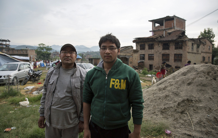 Nanda Gopal (left) and his son, Binay, in the ruins of Harishidi village.