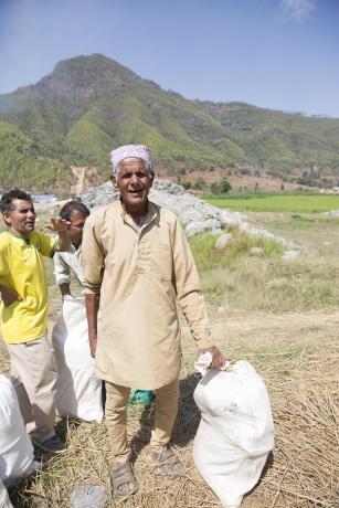 "Iswari Prasad Adhikari walked for two hours to get the food, kitchen kit, and blankets we provided.  ""It's really helpful for me,"" he said."