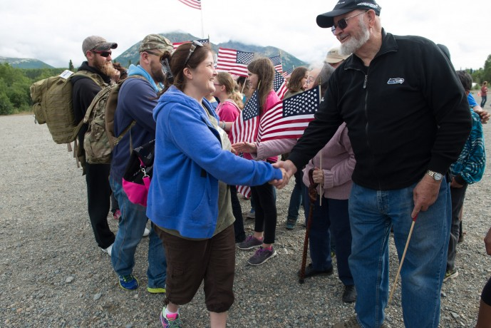 Couples are greeted by handshakes and waving flags as they arrive.