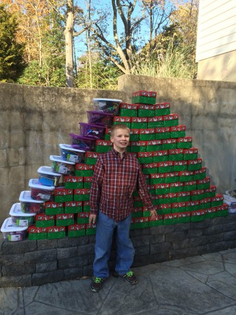 Brett with all of the shoeboxes that were packed for his eighth birthday party