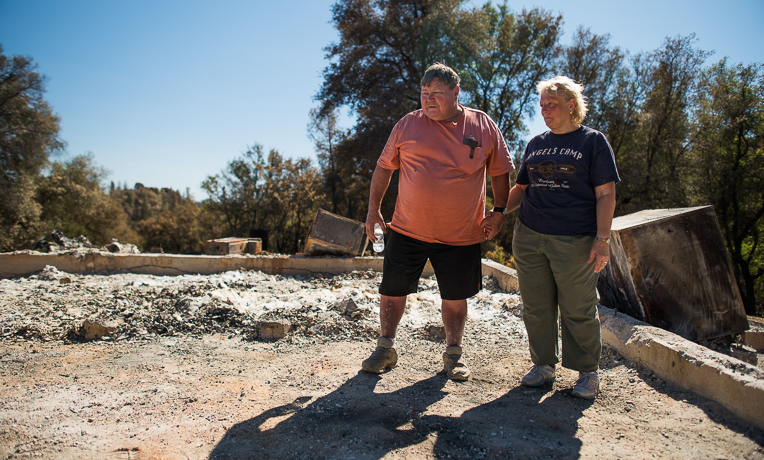 The Aharts look over the ruins of their home, which was destroyed by the Butte Fire.