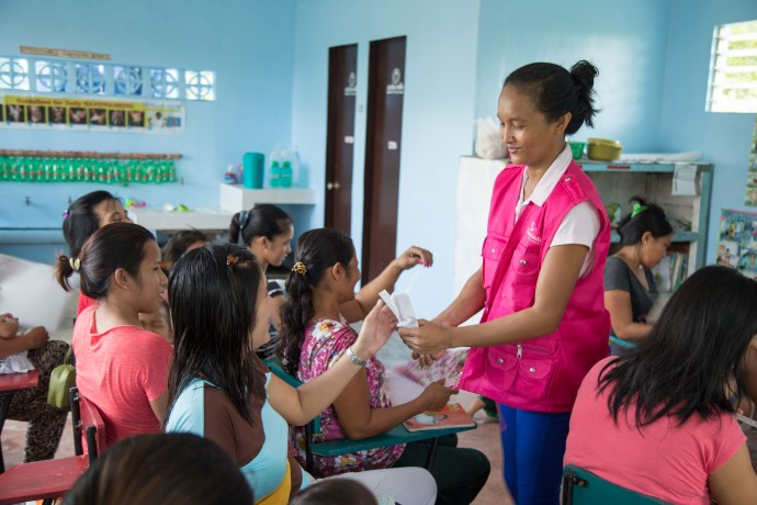 Rosemarie Natividad meets with 17 women in a San Juan classroom to teach important feeding practices in their mother-to-mother support group.