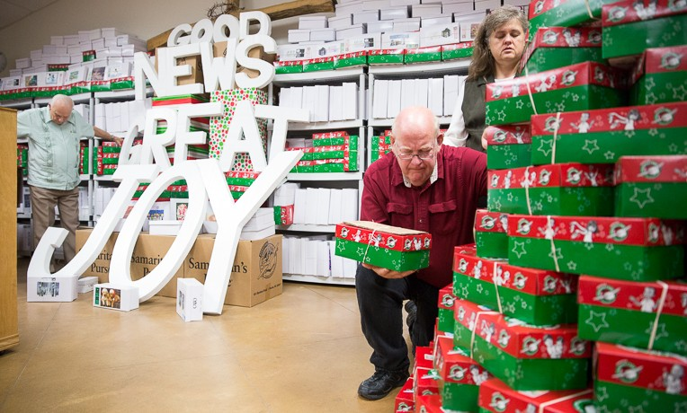 Cherry and Mark Brumbelow pray over Operation Christmas Child shoeboxes during a service at Grace Baptist Church.