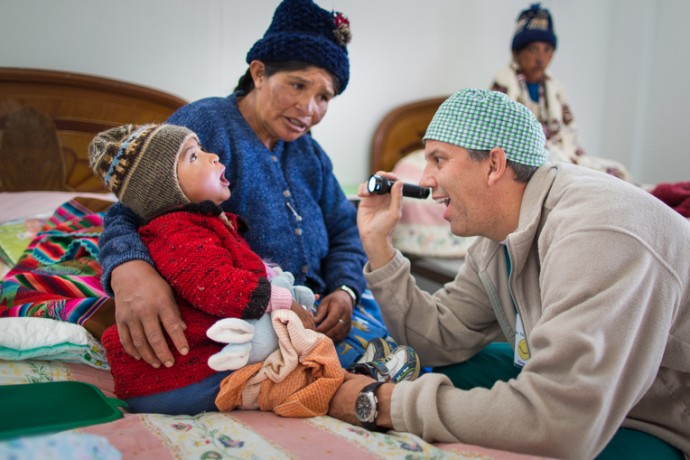 Dr. Tom Boeve, one of two surgeons who traveled to Bolivia with our team in late October, examines little Ana as her mother Sandusa watches.
