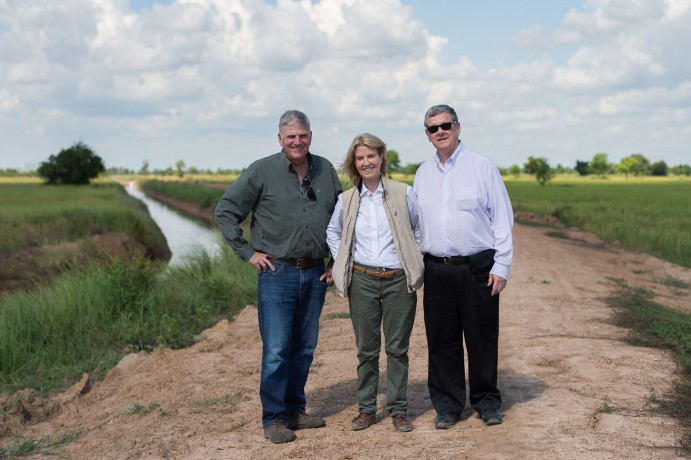 Franklin Graham, Greta Van Susteren, and John Coale stand in front of the new irrigation system.