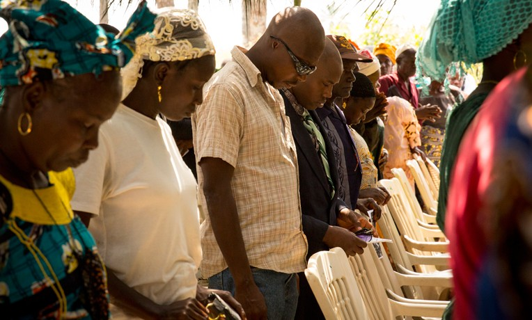 Participants at the Ebola Memorial Cemetery dedication in Foya, Liberia, join together in prayer.