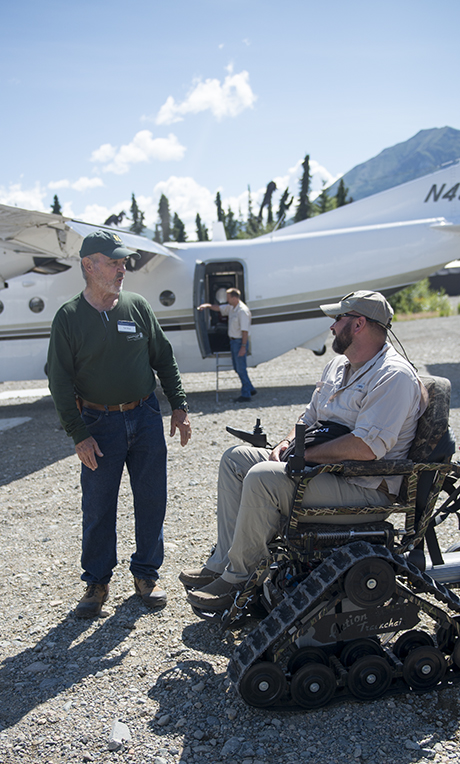 Tom Wollney on the runway in Alaska with one of our volunteer staff.