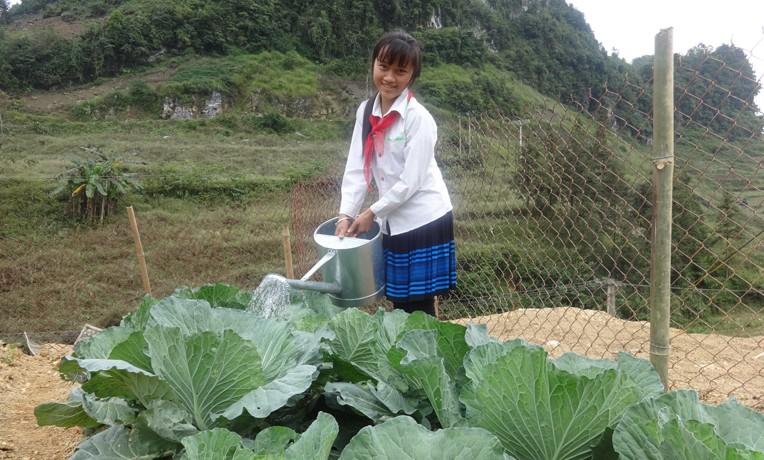 Di waters her garden at school in the highlands of Vietnam.