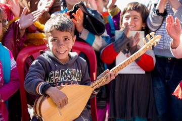 Boy smiles as he plays a traditional instrument.
