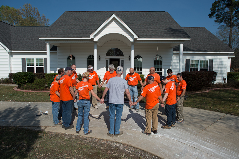 Orange-clad Samaritan' s Purse volunteers pray at the Ogle home in Monroe, Louisiana.