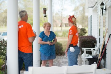 Carol Ogle talks with Samaritan's Purse volunteers on her front porch.