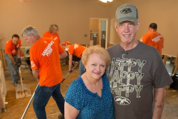 Royce and Carol Ogle stand in their flooded Louisiana home as Samaritan's Purse volunteers work in the background.