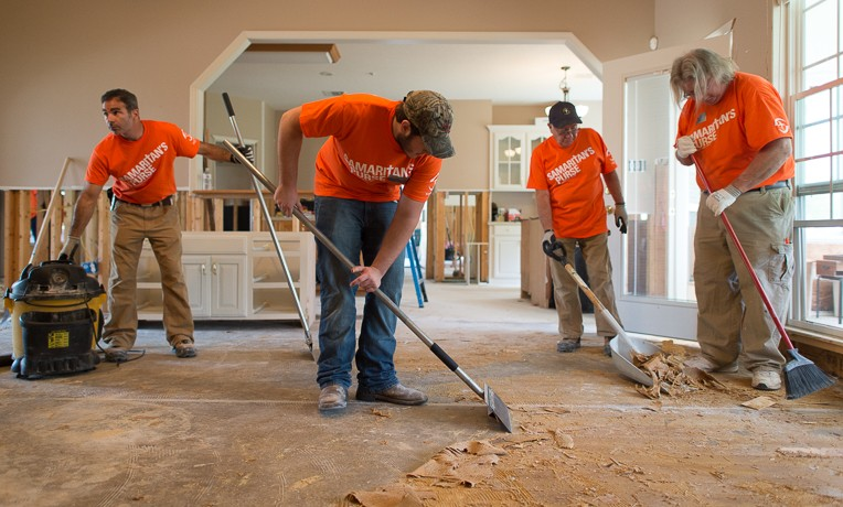 (from left to right) Steven Bruno, Stephen Wetzel, Mike Bruno, and Ted Painter at work scraping floors in the Ogle home.