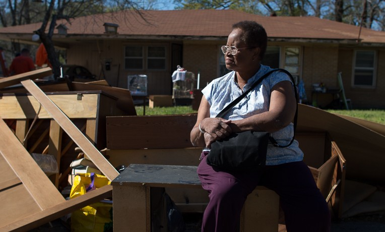 A homeowner sits near a pile of rubbish after flooding in Louisiana. She is being helped by Samaritan's Purse.