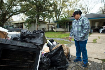 Louisiana, flooding, Samaritan's Purse, Cynthia Sanders looks over waterlogged belongings that had to be thrown away after her home flooded.